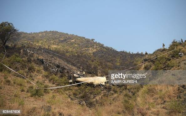 Pakistani soldiers cordon off the plane crash site in the village of Saddha Batolni in the Abbottabad district of Khyber Pakhtunkhwa province on...