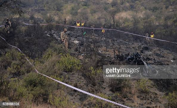 Pakistani soldiers cordon off the plane crash site near the village of Saddha Batolni in the Abbottabad district of Khyber Pakhtunkhwa province on...