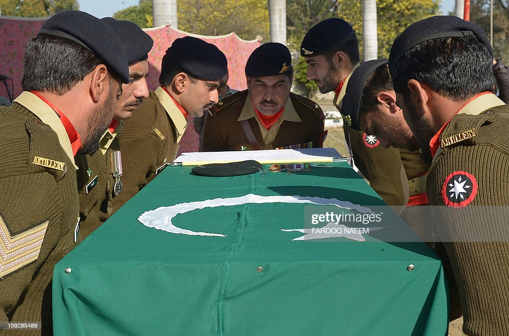 Pakistani soldiers place the coffin of their fallen comrade Havildar (Sargeant) Mohyuddin, who was allegedly shot by Indian troops at the Hotspring sector in Battal in Pakistan-administered Kashmir, during his funeral in Jhelum some 100 kms of Islamabad on January 11, 2013. Pakistan on January 11 summoned the Indian ambassador to Islamabad to protest against the death of another Pakistani soldier in what it said was a second cross-border attack from Indian troops in Kashmir. AFP PHOTO/FAROOQ NAEEM