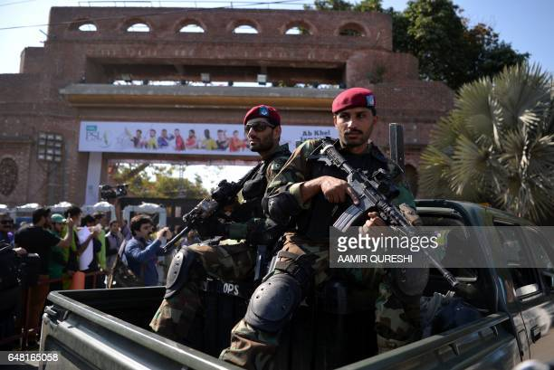 Pakistani soldiers sit in a vehicle as they patrol while cricket fans queue at an entry gate of The Gaddafi Cricket Stadium in Lahore on March 5 as...