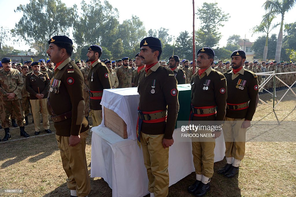 Pakistani soldiers stand beside the coffin of their fallen comrade Havildar (Sargeant) Mohyuddin, who was allegedly shot by Indian troops at the Hotspring sector in Battal in Pakistan-administered Kashmir, during his funeral in Jhelum some 100 kms of Islamabad on January 11, 2013. Pakistan said one of its soldiers was killed January 10 by 'unprovoked' Indian firing across their tense border in Kashmir, the third deadly incident reported in five days in the disputed region.