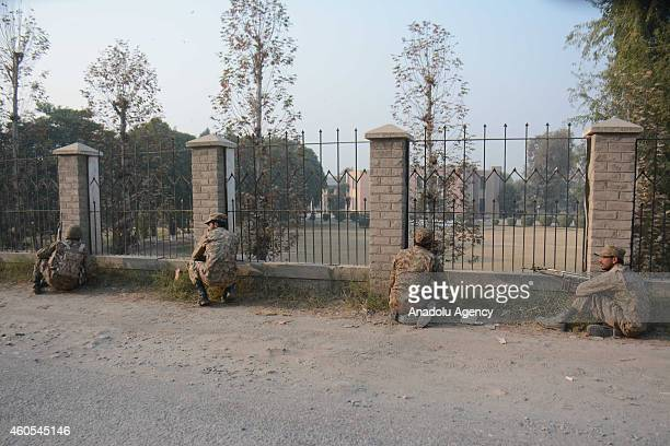 Pakistani soldiers stand guard near the site of an attack by Taliban gunmen on a school in the northwestern city of Peshawar Pakistan on December 16...