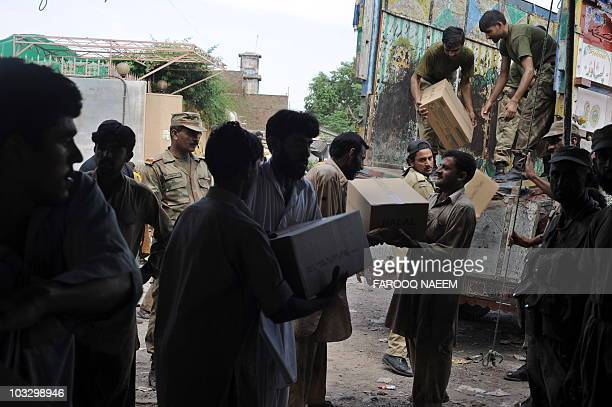 Pakistani soldiers unload reliefs supplies from a truck in Pabbi on August 3 2010 Desperate survivors crushed into relief centres after Pakistan's...