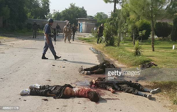 CONTENT Pakistani soldiers watch the bodies of Taliban attackers at the Pakistan Air Force base in Peshawar on September 18 2015 The death toll in a...