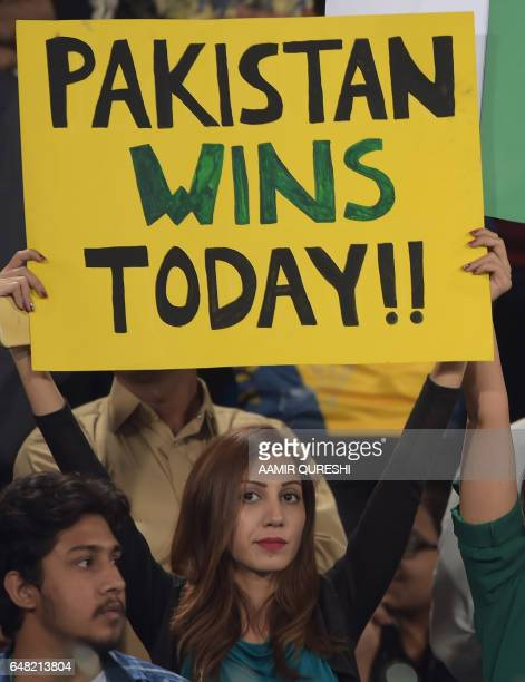 A Pakistani spectator holds a placard prior to the start of the final cricket match of the Pakistan Super League between Quetta Gladiators and...