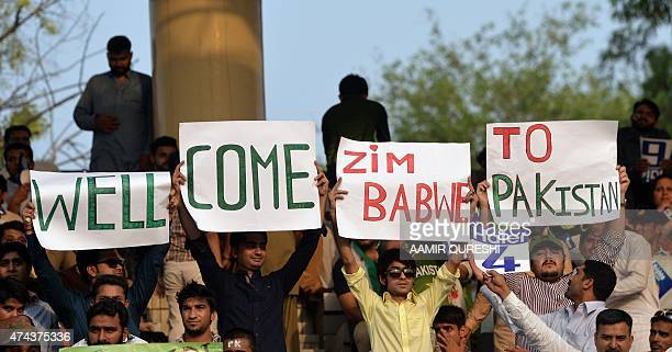 Pakistani spectators carry placards as they await the start of the first International T20 cricket match between Pakistan and Zimbabwe at the Gaddafi...