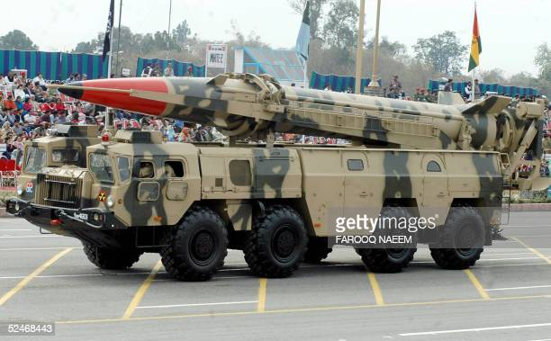 Pakistani spectators watch the Shaheen I mediumrange ballistic missile capable of carrying nuclear warhead is driving past with its launcher during...