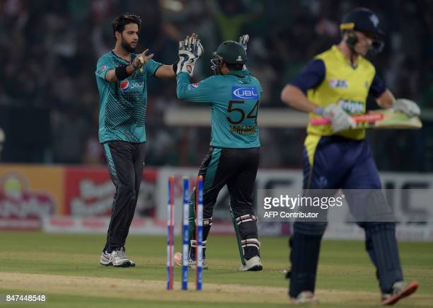 Pakistani spinner Imad Wasim celebrates with captain and wicketkeeper Sarfraz Ahmad after taking the wicket of World XI batsman George Bailey during...