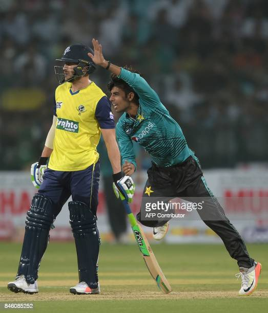 Pakistani spinner Shadab Khan delivers the ball next to World XI captain Faf du Plessis during the first Twenty20 international match between the...