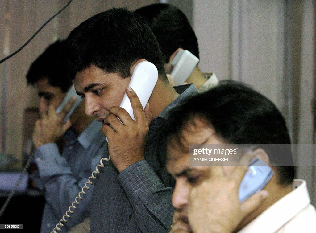A Pakistani stock dealers make phone calls at a brokerage house in Karachi, 20 May 2004. Pakistan stocks rose 0.72 percent on the news of incoming Indian Prime Minister Manmohan Singh's pledge to push forward a peace dialogue with Islamabad, analysts said. AFP PHOTO/Aamir QURESHI