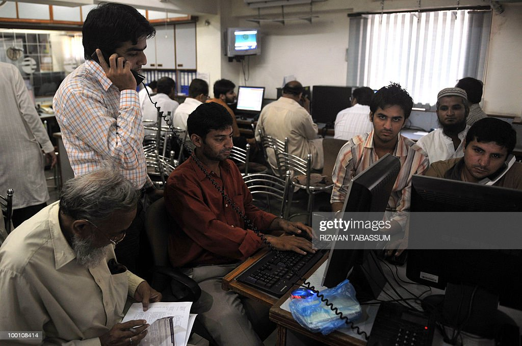 Pakistani stock dealers work at a brokerage house during a trading session in Karachi on May 21, 2010. The benchmark Karachi Stock Exchange (KSE) 100-index was 9881.65, down 111.75 points. AFP PHOTO/Rizwan TABASSUM