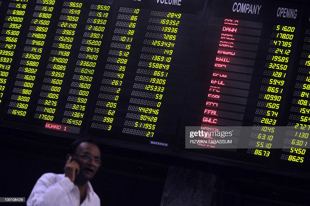 A Pakistani stockbroker talks on a phone underneath an index board during a trading session at the Karachi Stock Exchange (KSE) on May 21, 2010. The benchmark Karachi Stock Exchange (KSE) 100-index was 9881.65, down 111.75 points. AFP PHOTO/Rizwan TABASSUM