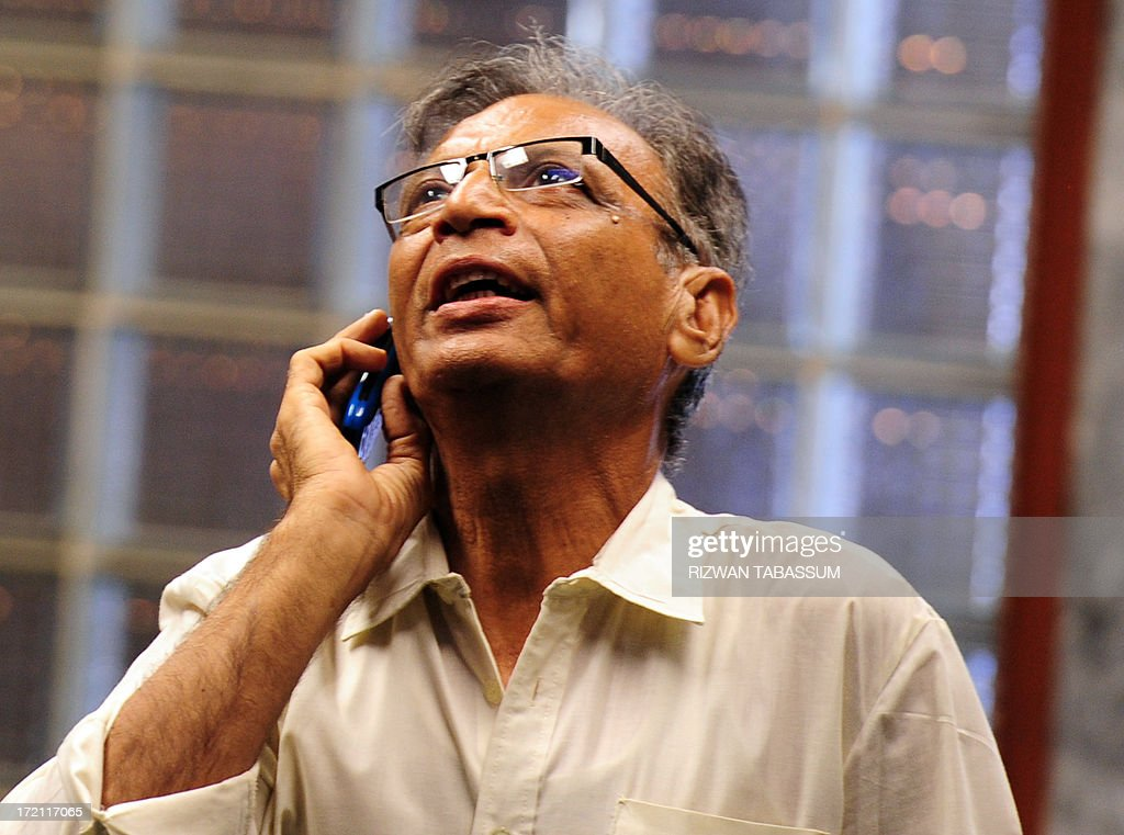 A Pakistani stockbroker talks on his cell phone as he watches the latest share prices during a trading session at the Karachi Stock Exchange (KSE) in Karachi on July 2, 2013. The benchmark KSE-100 index was 21640.63, with increase of 277.47 points in morning session. AFP PHOTO / Rizwan TABASSUM