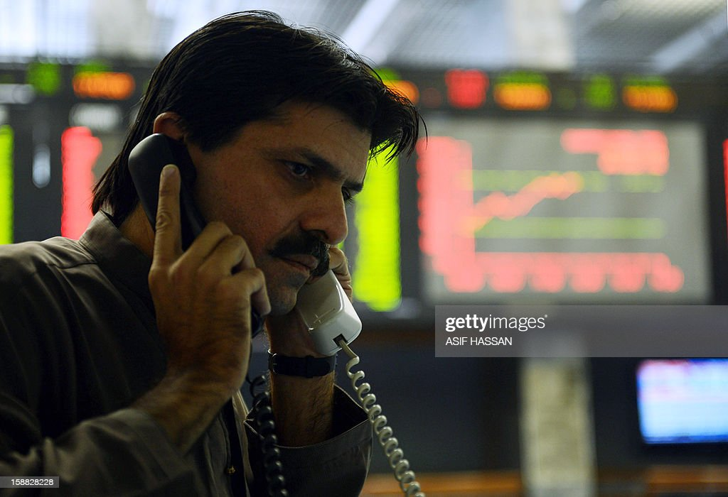 A Pakistani stockbroker talks on phones as he monitors share prices during the new year's eve trading session at the Karachi Stock Exchange (KSE) in Karachi on December 31, 2012. The KSE-100 Index broke 17,000 points barrier on the last day of calender year, gained 49 percent in 2012 and was placed among the top ten best performing markets globally. AFP PHOTO/Asif HASSAN