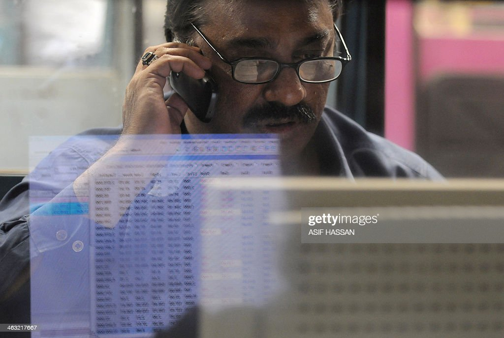 A Pakistani stockbroker talks on the phone as he monitors share prices at his desk during a trading session at the Karachi Stock Exchange (KSE) on January 17, 2014. The benchmark KSE-100 index 26913.85 , with increase of 183.61 points at end of the day. AFP PHOTO / Asif HASSAN