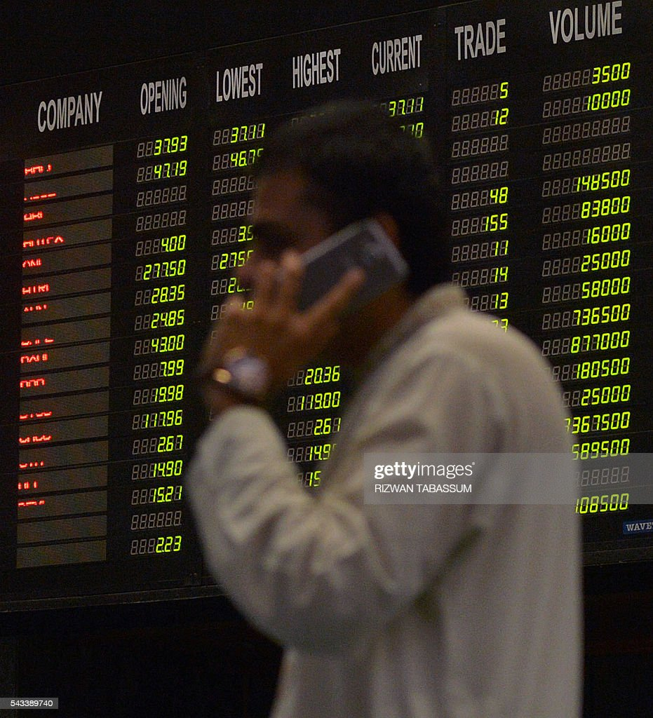 A Pakistani stockbroker talks on the phone next to an index board during a trading session at the Pakistan Stock Exchange (PSE) in Karachi on June 28, 2016. The benchmark PSE-100 index was 36877.86, down 161.71 points in the morning session as global markets reeled from the Brexit-induced financial and political chaos. / AFP / RIZWAN