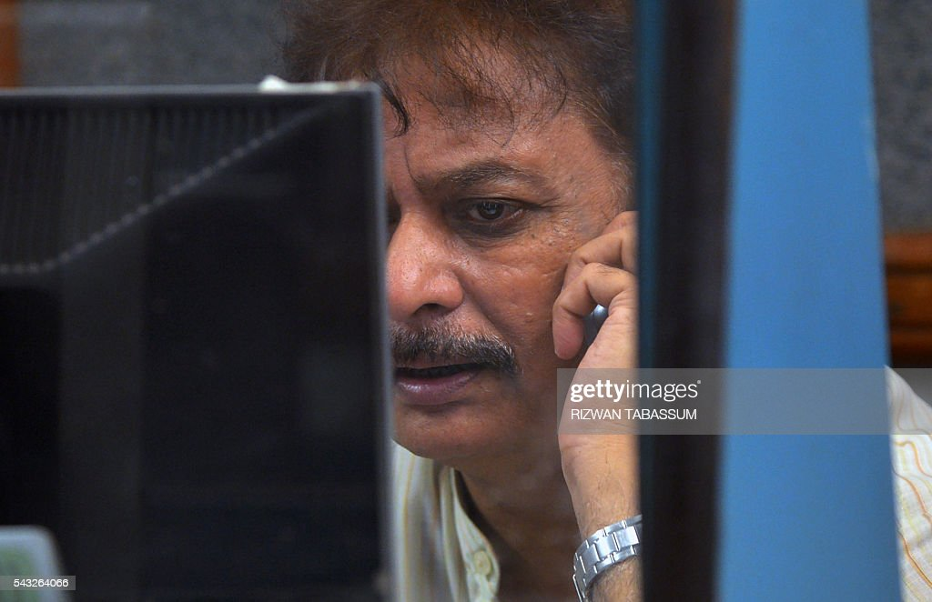 A Pakistani stockbroker watches share prices on a monitor during a trading session at the Pakistan Stock Exchange (PSE) in Karachi on June 27, 2016. The benchmark PSE-100 index was 37167.43, down 222.45 points in the morning session as global markets reeled from the Brexit-induced financial and political chaos. / AFP / RIZWAN