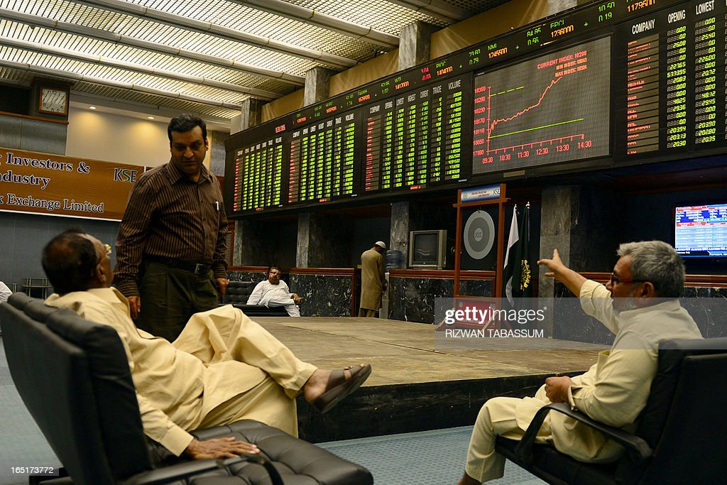 Pakistani stockbrokers discuss as they monitor share prices during a trading session at the Karachi Stock Exchange (KSE) in Karachi on April 1, 2013. The benchmark KSE-100 index was 18292.07, with an increase of 248.76 points in mid of the day's session. AFP PHOTO/Rizwan TABASSUM