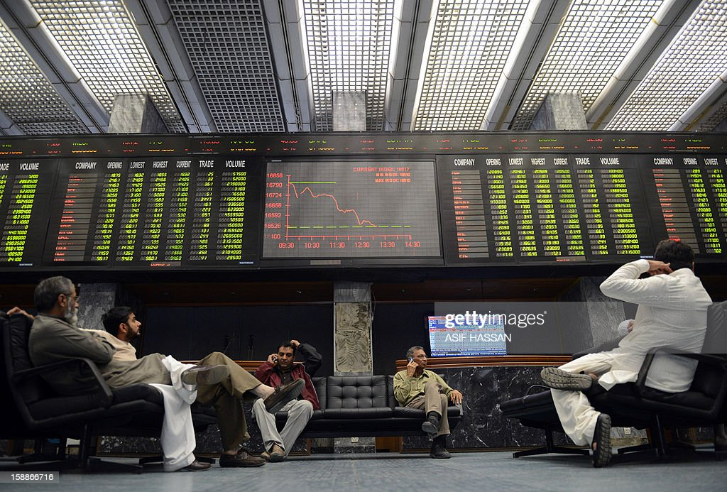 Pakistani stockbrokers monitor share prices on a digital board during a trading session at the Karachi Stock Exchange (KSE) in Karachi on January 2, 2013. The benchmark KSE-100 index was 16447.21, down 347.66 points in mid of the day's session. AFP PHOTO/ Asif HASSAN