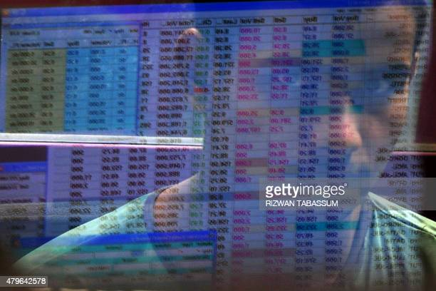A Pakistani stockbroker's reflection is seen appears on a share prices board during trading session at the Karachi Stock Exchange in Karachi on July...