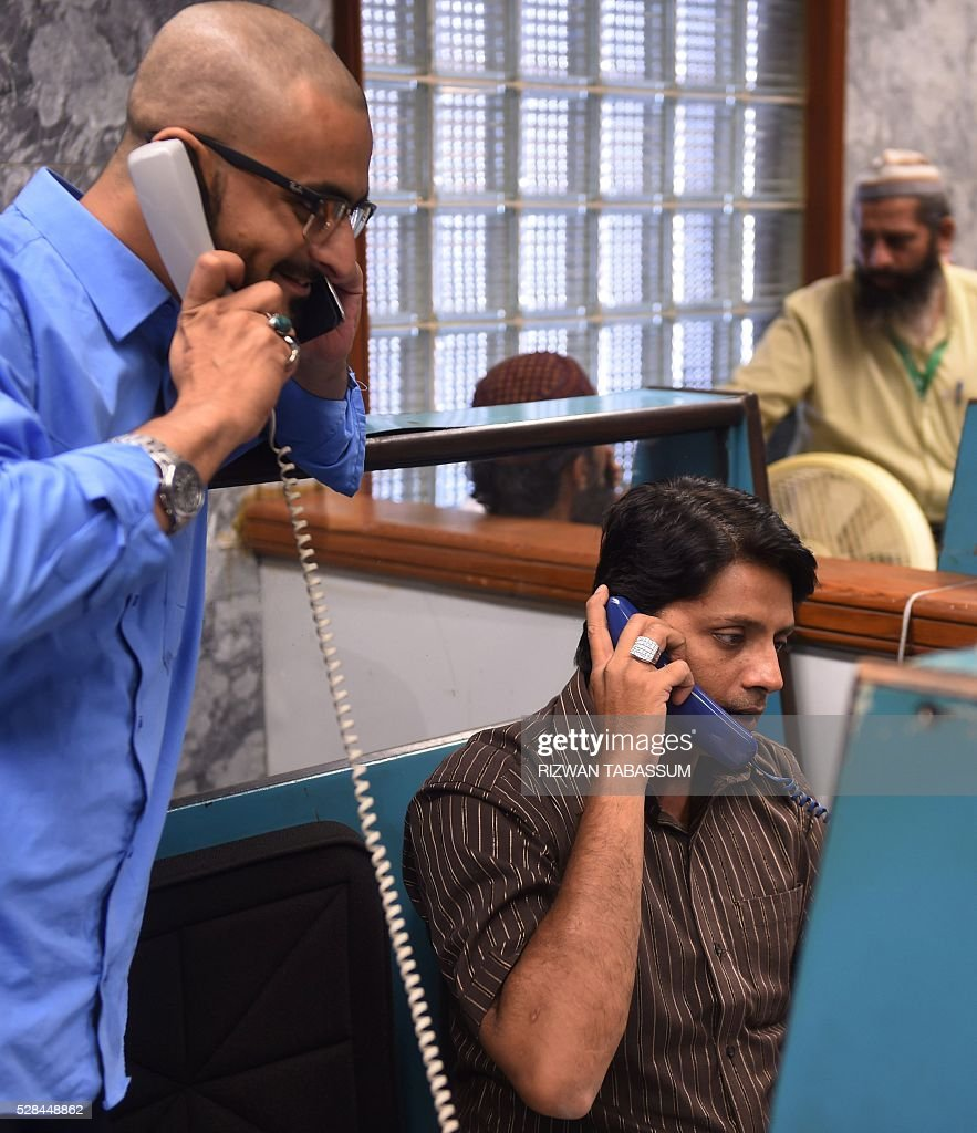Pakistani stockbrokers talk to clients as they monitor share prices during a trading session at the Pakistan Stock Exchange (PSE) in Karachi on May 5, 2016. The benchmark PSE-100-Index closed at 35941.47, up 623.91 points at the end of the day's trade. / AFP / RIZWAN