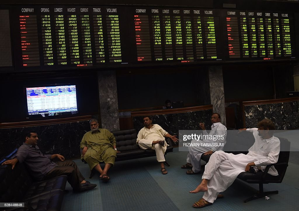 Pakistani stockbrokers talk under an index board during a trading session at the Pakistan Stock Exchange (PSE) in Karachi on May 5, 2016. The benchmark PSE-100-Index closed at 35941.47, up 623.91 points at the end of the day's trade. / AFP / RIZWAN