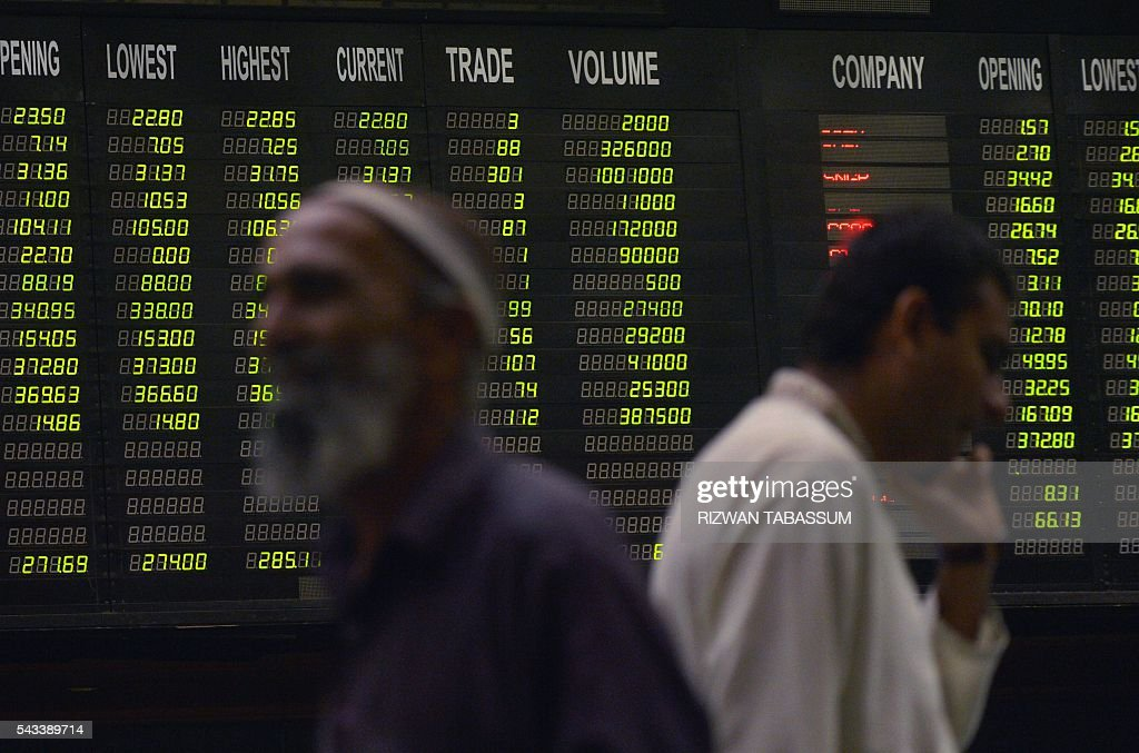 Pakistani stockbrokers walk past an index board during a trading session at the Pakistan Stock Exchange (PSE) in Karachi on June 28, 2016. The benchmark PSE-100 index was 36877.86, down 161.71 points in the morning session as global markets reeled from the Brexit-induced financial and political chaos. / AFP / RIZWAN