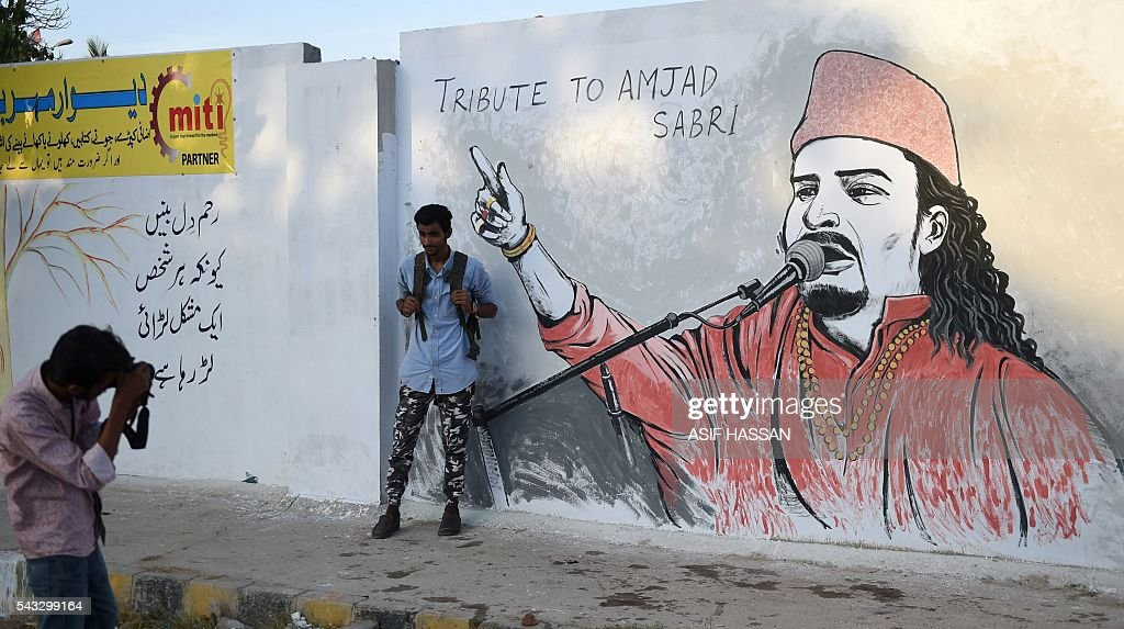 A Pakistani student takes a photograph of his friend next to a wall image of late Sufi musician Amjad Sabri in Karachi on June 27, 2016. One of Pakistan's best known Sufi musicians Amjad Sabri was shot dead by unknown assailants riding a motorcycle in Karachi on June 22, triggering an outpouring of grief over what police described as an 'act of terror'. / AFP / ASIF