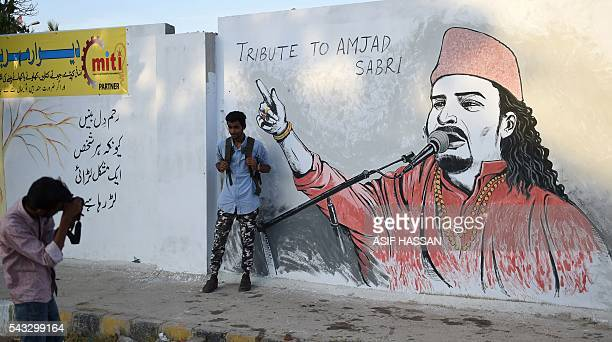 A Pakistani student takes a photograph of his friend next to a wall image of late Sufi musician Amjad Sabri in Karachi on June 27 2016 One of...