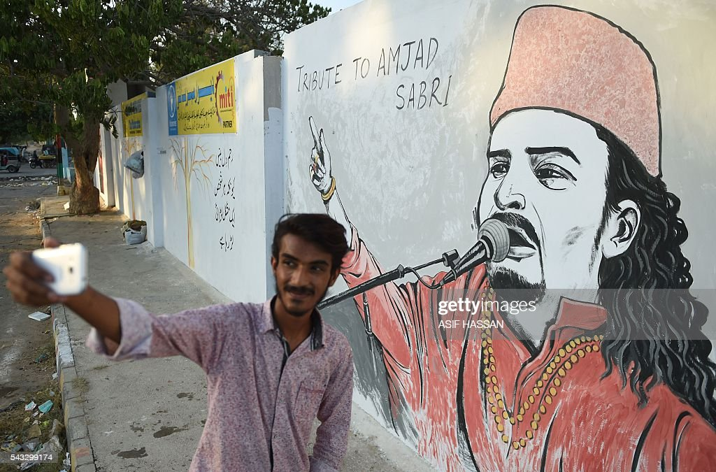 A Pakistani student takes a selfie photograph next to a wall image of late Sufi musician Amjad Sabri in Karachi on June 27, 2016. One of Pakistan's best known Sufi musicians Amjad Sabri was shot dead by unknown assailants riding a motorcycle in Karachi on June 22, triggering an outpouring of grief over what police described as an 'act of terror'. / AFP / ASIF