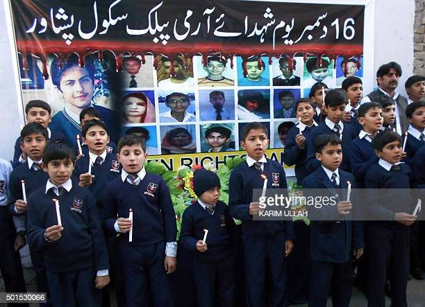 Pakistani students hold candles as they mark the first anniversary of the Peshawar school massacre which left more than 150 people dead at a school...