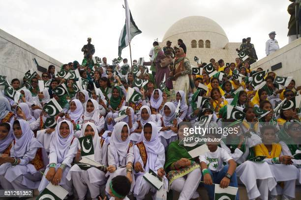 Pakistani students hold national flags during a ceremony at the mausoleum of Pakistan's founder Mohammad Ali Jinnah to mark the country's...