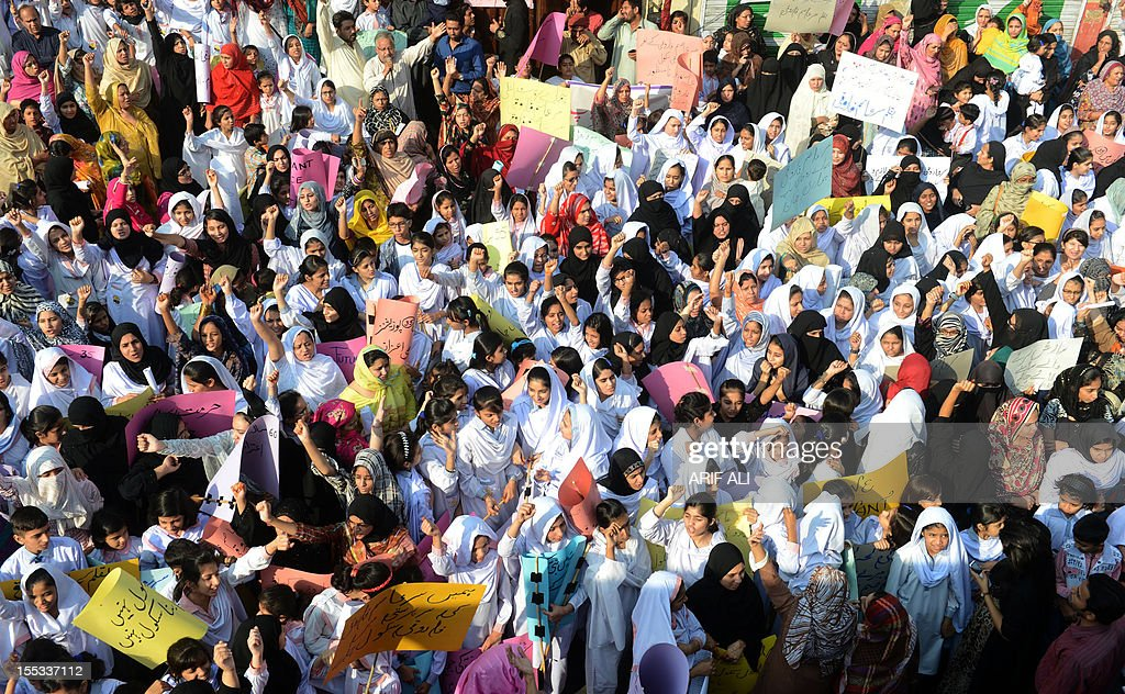 Pakistani students of Farooqi Girls' High School wave placards as they stage a protest in Lahore on November 3, 2012, demanding the re-opening of their school that was set fire by an angry mob, who alleged the school gave a test that insulted the Prophet Mohammed. A Pakistani teacher at the centre of a blasphemy row was in hiding, as her school management denied all responsibility for the 'dirty act' and called for her to be punished. AFP PHOTO/Arif ALI