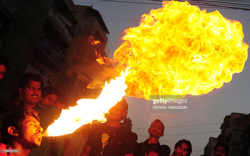 A Pakistani Sunni Muslim spits fire during an Ashura procession on the tenth day of the holy month of Moharram, to mark the martyrdom of seventh century saint Imam Hussain in Karachi on November 25, 2012. A bomb attack on a Shiite Muslim procession killed five mourners and wounded more than 80 in northwest Pakistan on November 25 as Shiites marked their holiest day Ashura, officials said.