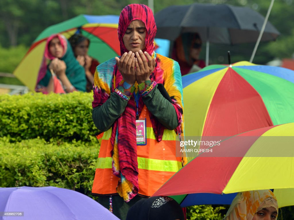 A Pakistani supporter of Canada-based preacher Tahir-ul-Qadri prays as she and others gather for congregational Friday prayers held at an anti-government protest site in front of the Parliament in Islamabad on August 22, 2014. Pakistani opposition politician Imran Khan called August 21 off talks with the government aimed at ending protests seeking the fall of the prime minister, which have unnerved the nuclear-armed nation. Khan and populist cleric Tahir-ul-Qadri have led followers protesting outside parliament for the past two days demanding Prime Minister Nawaz Sharif quit. AFP PHOTO/ Aamir QURESHI