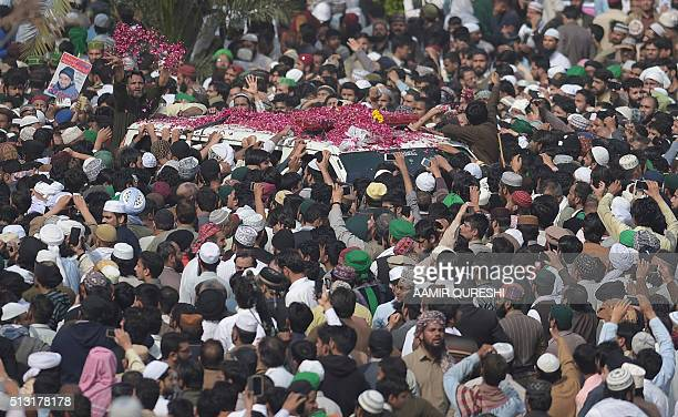 A Pakistani supporter of convicted murderer Mumtaz Qadri showers rose petals on the ambulance carrying Qadri's body during his funeral prayers a day...