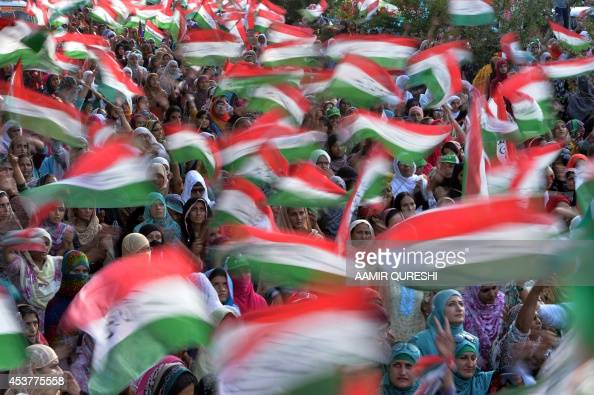 Pakistani supporters of Canadabased preacher TahirulQadri wave flags as they listen to speech his speech during a protest march against the country's...