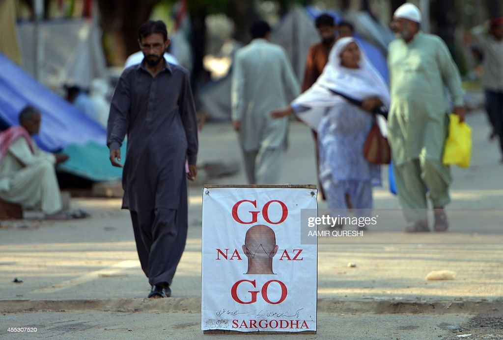 Pakistani supporters of Canadian cleric Tahir ul Qadri walk past a placard against Prime Minister Nawaz Sharif placed in the middle of a street in...