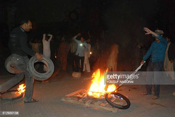 Pakistani supporters of former police bodyguard Mumtaz Qadri torch tyres on a street during a protest against the execution of Qadri in Hyderabad on...