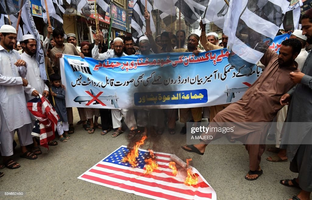 Pakistani supporters of the banned organisation Jamaat-ud-Dawa (JuD) burn a US flag in a protest in Peshawar on May 27, 2016, against the US drone strike on Pakistani soil that killed Taliban leader Mullah Akhtar Mansour. A US drone strike killed Taliban chief Mullah Akhtar Mansour in a remote area in Pakistan along the border with Afghanistan, the first known American assault on a top Afghan Taliban leader on Pakistani soil. / AFP / A