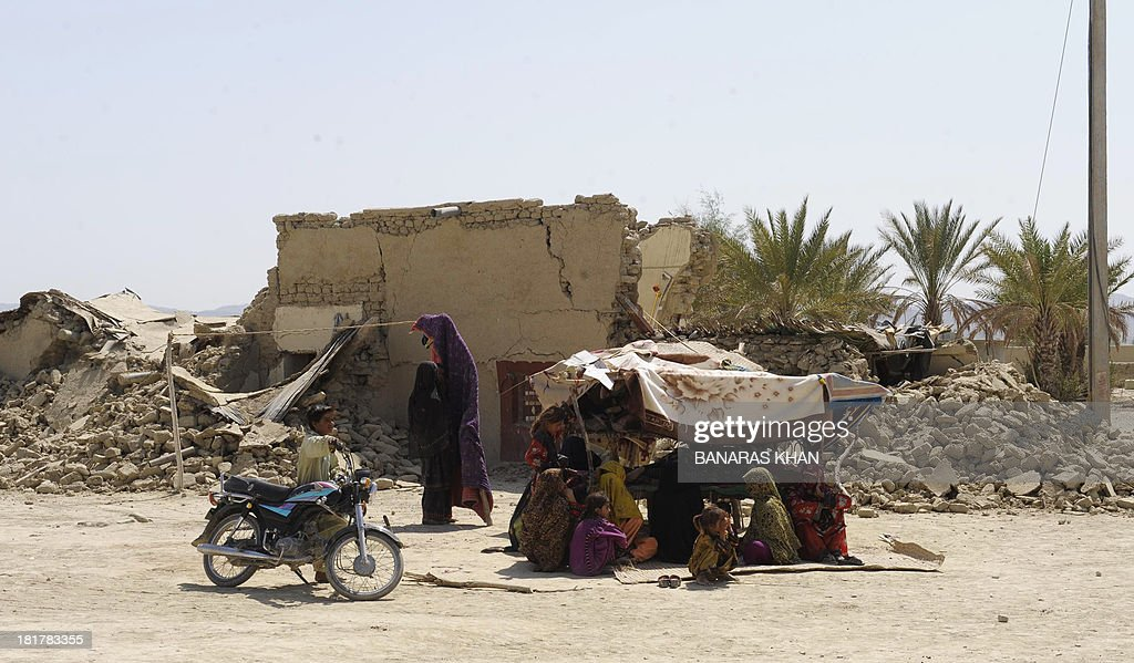 Pakistani survivors sit under a makeshift shelter in the earthquake-devastated district of Awaran on September 25, 2013. Desperate villagers in southwest Pakistan clawed through the wreckage of their ruined homes , a day after a huge earthquake struck, killing more than 270 people and creating a new island off the coast. AFP PHOTO/Banaras KHAN