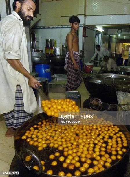 A Pakistani sweet maker prepares 'Gulab Jamun' a traditional sweet ahead of Eid alFitr at a shop in Karachi 24 October 2006 Pakistani Muslims will...