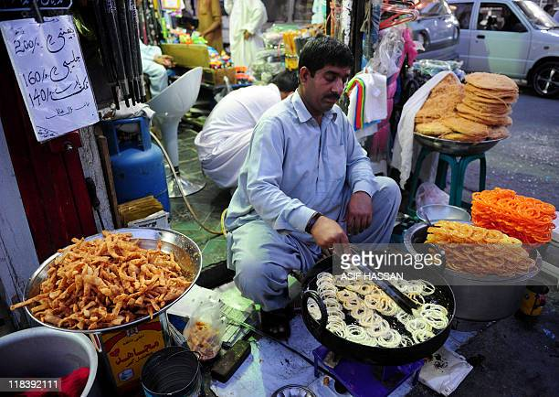 A Pakistani sweets maker Bilal prepares jalebi a popular dessert at his roadside stall on May 14 in Abbottabad the city where Osama bin Laden was...