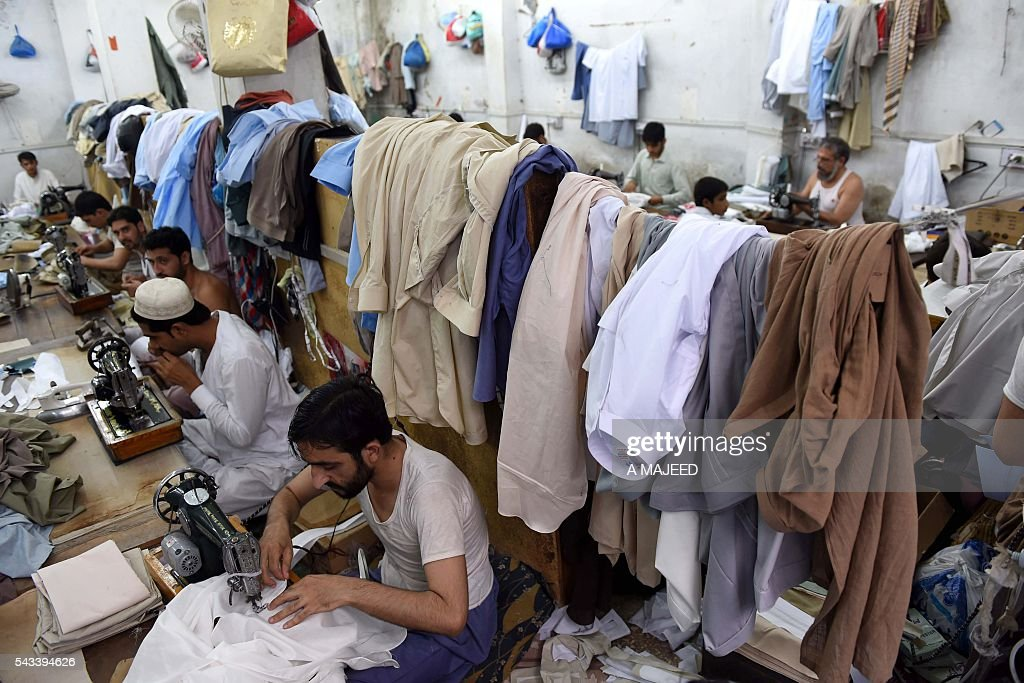 Pakistani tailors stitch clothing in preparation for the forthcoming Eid al-Fitr Festival marking the end of the holy month of Ramadan, at a market in Peshawar on June 28, 2016 For Muslims the world over, Ramadan, held in the ninth month of the Islamic calendar, is a time of worship and contemplation during which a fast is observed from dawn until dusk. / AFP / A