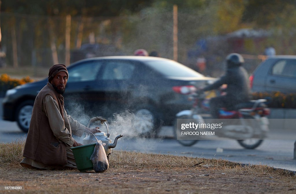 A Pakistani tea vendor prepares tea near a traffic signal in Islamabad on December 1, 2012. Pakistan's growth remains too weak, underlying inflation is high and the trade balance is heading in the wrong direction, the IMF said in a statement. AFP PHOTO/ Farooq NAEEM