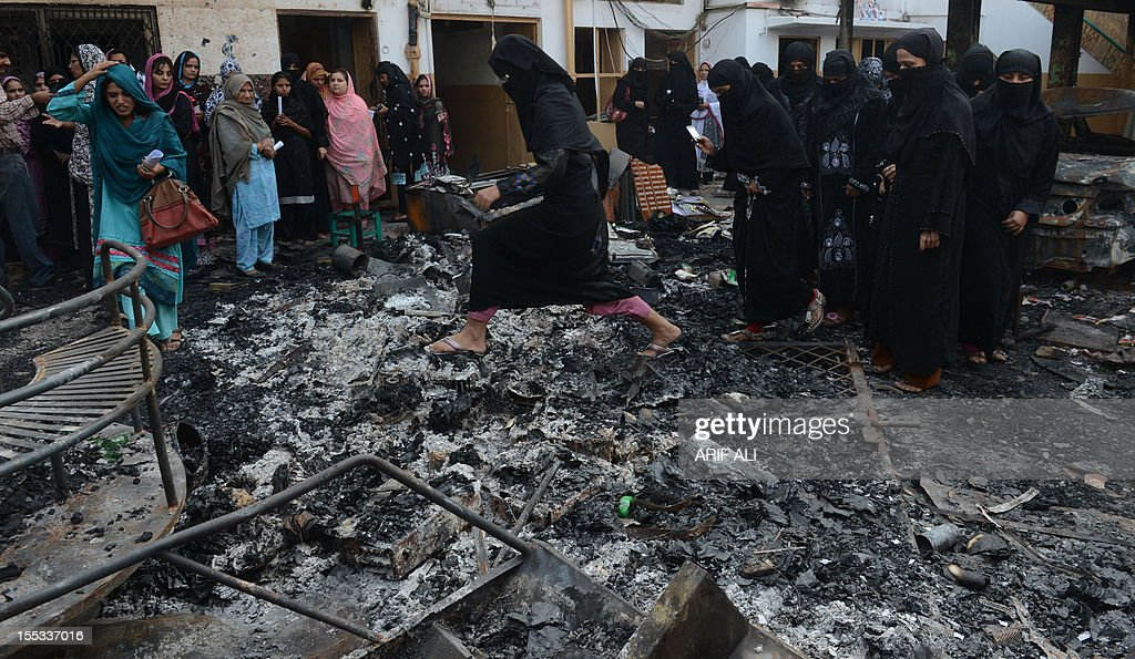Pakistani teachers inspect the wreckage of a burnt school in Lahore on November 3, 2012, after it was set on fire by an angry mob alleging that the school gave a test that insulted the Prophet Mohammed. A Pakistani teacher at the centre of a blasphemy row was in hiding as her school management denied all responsibility for the 'dirty act' and called for her to be punished. AFP PHOTO/Arif ALI