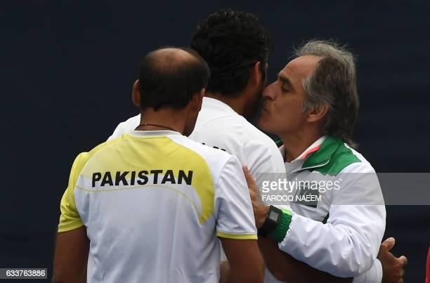 Pakistani tennis coach Rashid Ahmad Malik kisses AisamUlHaq Qureshi next to team member Aqeel Khan during their men's doubles match against Iran in...