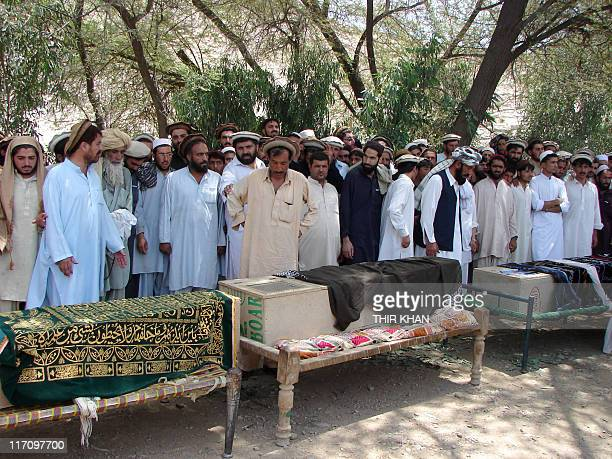 Pakistani tribesmen gather for funeral prayers before the coffins of people allegedly killed in a US drone attack claiming that innocent civilians...