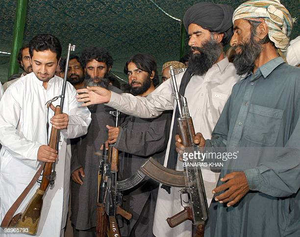 Pakistani tribesmen hand over their weapons to Baluchistan Provincial Home Minister Shoaib Nosherwani during a surrender ceremony in Quetta 29 June...