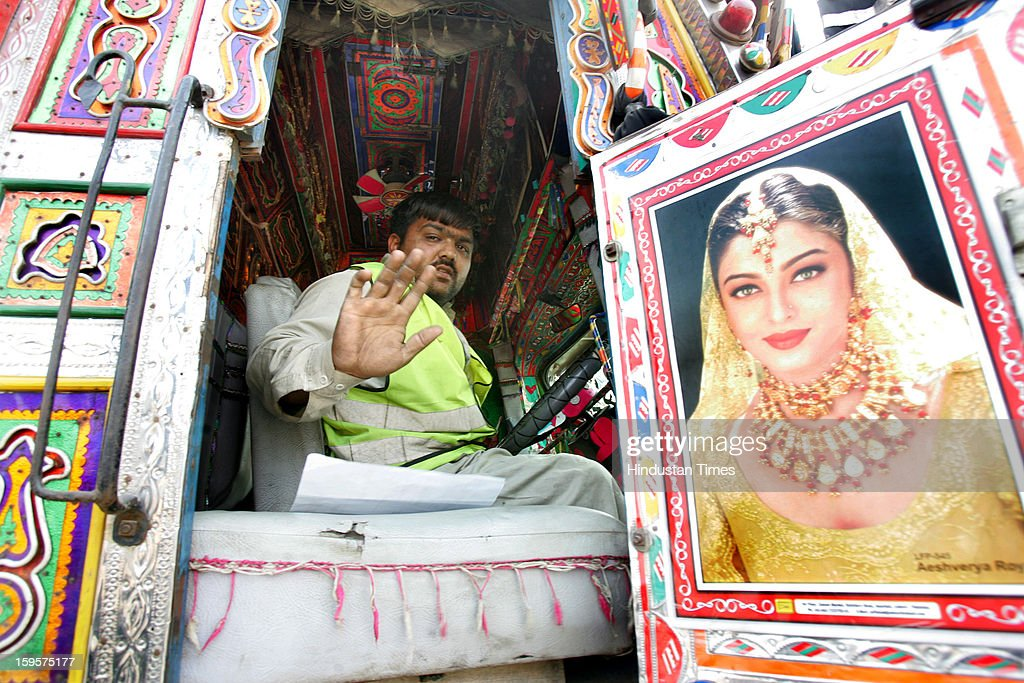 A Pakistani truck driver, Jaweed Hussain, who framed the portrait of Indian Heroine Ashverya Rai Bachchan on his truck window, waves as he leaves back for his nation after unloading the importable goods in India at Integrated Check Post (ICP) along with India-Pakistan border Attari, on January 16, 2013 near Amritsar, India. The hot words war from the both sides of the border created fear among the truck drivers whose livelihood depends upon trade between the two countries.